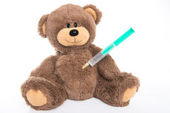 Teddybär mit Spritze im Magen Stockbild