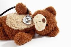 Teddybär mit Stethoskop auf weißem Hintergrund Stockbilder
