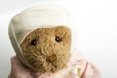 Teddybär mit Verband auf dem Kopf Stockbild