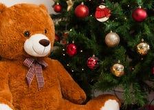 Teddybär nahe Weihnachtsbaum mit Geschenken Stockbild