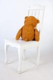 Teddybär sitzt auf einem Stuhl Stockfotos