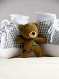 Teddybär und Babyschuhe lizenzfreies stockfoto