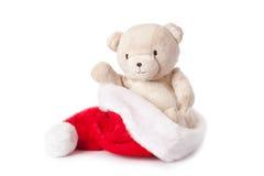 Teddybär und Weihnachtsschutzkappe Stockfotos