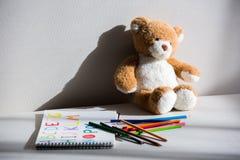 Teddybär- und Zeichnungsalbum mit bunten Bleistiften Lizenzfreie Stockfotos