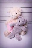 Teddybären, die auf weißem Bretterboden mit dem netten Hintergrund einsam sitzen Stockfotos