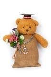 Teddybärspielzeug, das eine Blume in seinen Armen erfasst lizenzfreies stockbild