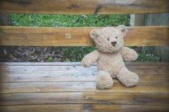 Teddybear坐一条长凳在公园 免版税图库摄影