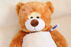 Teddybear in Bed. Photo of a sick teddybear with a plaster in bed Stock Image