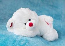 Teddybear sleeping on a soft blanket. Teddy bear stuffed toy sleeping on a soft blue velvet blanket Royalty Free Stock Photos