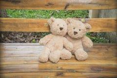 Teddybears坐一条长凳在公园 免版税库存图片