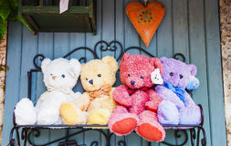 Teddybears on a shelf. Teddybears of different colors with bow ties sitting on a shelf stock photos