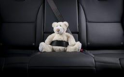 Teddybeer in de achterbank van een auto wordt vastgemaakt die Royalty-vrije Stock Foto's