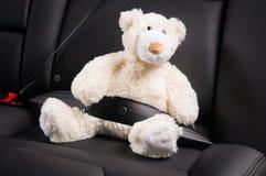 Teddybeer in de achterbank van een auto wordt vastgemaakt die Stock Foto's