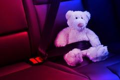 Teddybeer in de achterbank wordt vastgemaakt die Stock Fotografie