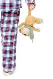 Teddybeer in de hand van een vrouw die naar slaap op een wit gaat stock fotografie