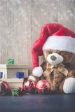 Teddybeer die een zitting van de santahoed naast giftdozen dragen met s royalty-vrije stock fotografie
