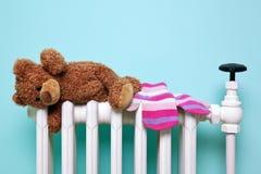 Teddybeer en handschoenen op een oude radiator Royalty-vrije Stock Afbeeldingen
