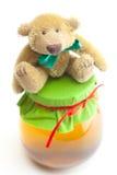 Teddybeer en kruik honing Stock Foto's