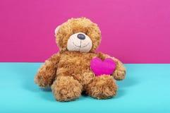 Teddybeer met gevoeld hart op twee kleurenachtergrond stock afbeelding
