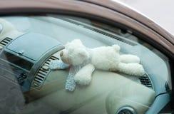 Teddybeer verlaten in een rode auto stock foto