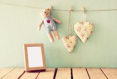 Teddybär über hölzerner Tabelle nahe bei Fotorahmen- und -gewebeherzen Retro- gefiltertes Bild Lizenzfreie Stockfotografie
