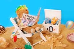Teddybär, der auf dem Strand sich entspannt Stockfotografie