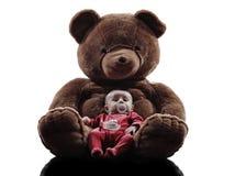 Teddybär, der sitzendes Schattenbild des Babys umarmt Lizenzfreie Stockfotografie