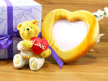 Teddybärbraunbär und rotes Herz formen mit Herzform-Fotorahmen Stockbilder