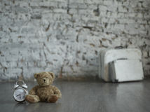Teddytime. Teddy bear sitting on the floor next to the clock against a white brick wall and suitcases Royalty Free Stock Photo