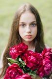 Teder meisje die met blauwe ogen zachte purpere pioen houden Stock Foto
