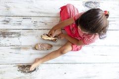 Teder meisje die op haar gouden pantoffels zetten stock fotografie
