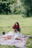 Teder meisje op een picknick die zachte purpere pioen houden Royalty-vrije Stock Foto