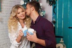 Teder paar in elegante kleren, die naast Kerstboom bij comfortabel huis zitten Stock Foto's
