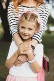 Tedere glimlachende dochter die haar houdende van moeder koesteren stock foto's