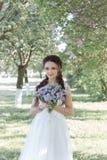 Tedere mooie leuke meisjesbruid in een witte luchtkleding met een boeket van seringen in haar handen die door het park op zonnig  Stock Foto's