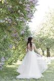 Tedere mooie leuke meisjesbruid in een witte luchtkleding met een boeket van seringen in haar handen die door het park op zonnig  Stock Fotografie