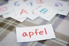 Tedesco; Apprendimento della parola nuova con le carte di alfabeto; Scrittura del A Fotografie Stock