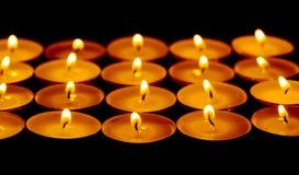 Tee beleuchtet Kerzen mit Feuer Stockfotos