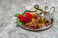 Tee, Dattelfrüchte, Rotrosenblume, Quran der Heiligen Schrift und Rosenbeet Lizenzfreie Stockfotos
