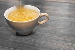 Tee, der in Cup ausläuft Lizenzfreies Stockbild