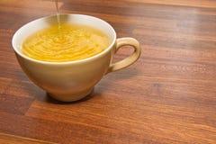 Tee, der in Cup ausläuft Lizenzfreies Stockfoto