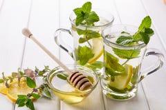Tee der frischen Minze mit zwei Glasschalen mit Zitrone und Honig Stockfotografie