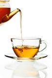 Tee, der in Glascup ausläuft stockfotografie