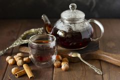 Tee in der Glasschale mit Teekanne nahe, Vanillehülse und Haselnuss am hölzernen Hintergrund, mit Löffel und Sieb nahe stockbilder