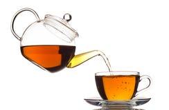 Tee, der im Cup ausläuft Lizenzfreie Stockfotos