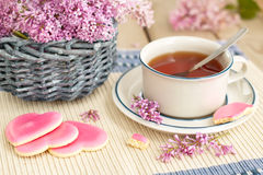 Tee, der mit rosa Plätzchen trinkt Stockbild