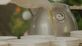 Tee, der in Teecup ausgelaufen wird Kessel gießt Tee in Schalen Lizenzfreies Stockfoto