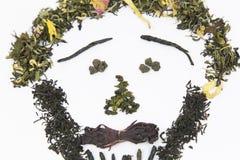 Tee der unterschiedlichen Vielzahl wird auf einem weißen Hintergrund in Form eines Bildes - ein Person ` s Gesicht ausgebreitet!  stockbilder