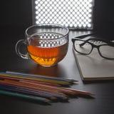Tee in einem Glasbecher, in den Bleistiften und in einem Notizbuch auf einer schwarzen Tabelle Lizenzfreie Stockfotografie
