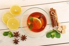 Tee in einem transparenten Becher mit Zitrone und Zimt und tadellose Blätter Stockfoto